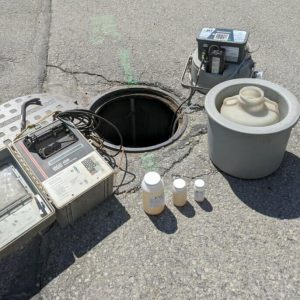 Field Sampling & Monitoring - Open Manhole Cover with Testing Equipment